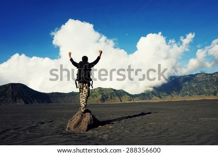 Hiker with backpack standing on of a mountain with raised hands and enjoying panoramic - stock photo