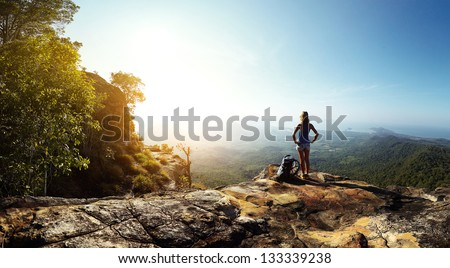 Hiker with backpack standing on top of a mountain and enjoying stunning valley view - stock photo