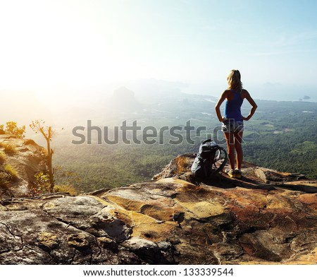Hiker with backpack standing on top of a mountain and enjoying valley view - stock photo