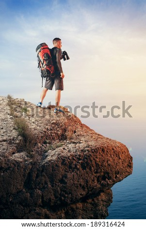 Hiker with backpack standing on top of a mountain and looking at the landscape through binoculars - stock photo