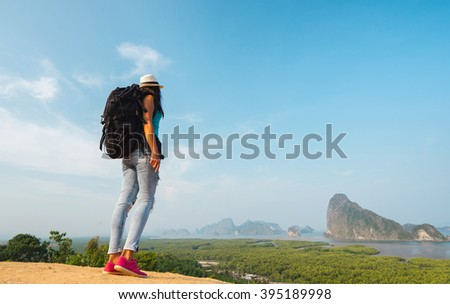 Hiker with backpack standing on top of the mountain and enjoying valley view - stock photo