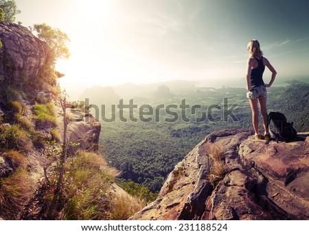 Hiker with backpack standing on top of the mountain and enjoying valley view at sunrise - stock photo
