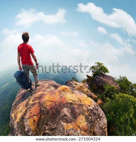Hiker with backpack standing on top of the mountain at sunny day - stock photo