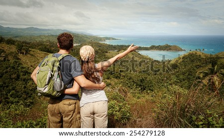 Hiker with backpack standing on top of the mountain with raised hands and enjoying valley view - stock photo