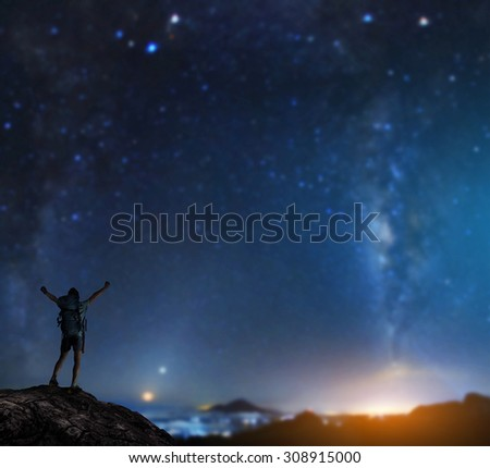Hiker with backpack standing on top of the mountain with raised hands with starry sky on the background - stock photo