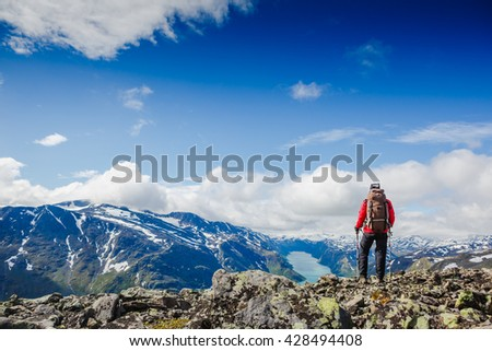 hiker with backpack traveling in Norway mountains