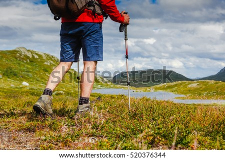 Hiker with backpack walking in Norway mountains. Fitness and healthy lifestyle outdoors