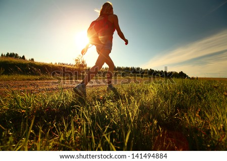 Hiker with backpack walking on a gravel road - stock photo