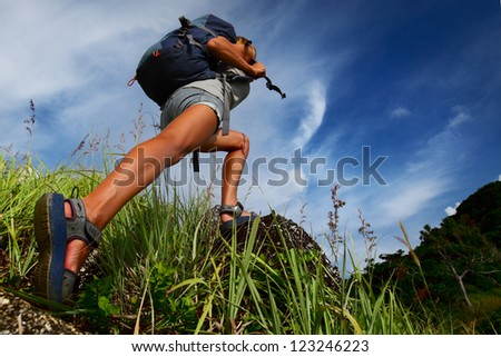 Hiker with backpack walking on a rocky terrain with green lush grass