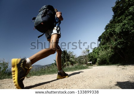Hiker with backpack walking on rural road with trees on sides - stock photo