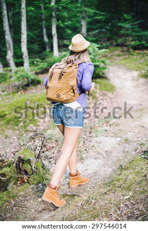 Hiker with backpack walking through forest. Hipster woman. Shallow depth of field. Focus on backpack - stock photo