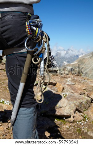 Hiker with climbing equipment in the mountains - stock photo
