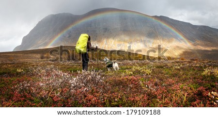 Hiker with dog, backpack and rainbow on a rainy day - stock photo