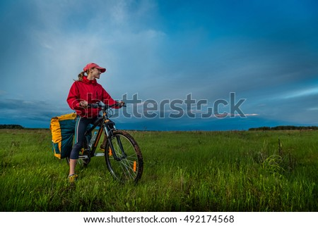 Hiker with loaded bicycle on a green summer meadow