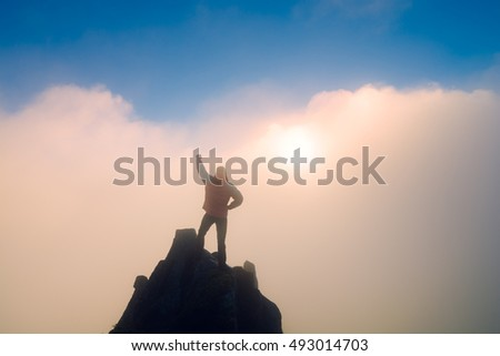 Hiker with raised hand standing on a cliffs edge. The top of the mountain. Colorful clouds in a light of sunrise.