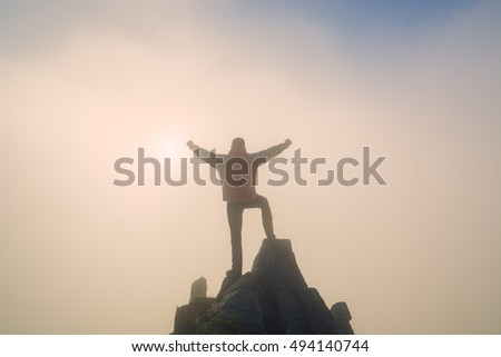 Hiker with raised hands standing on a cliffs edge. The top of the mountain. Colorful clouds in a light of sunrise.
