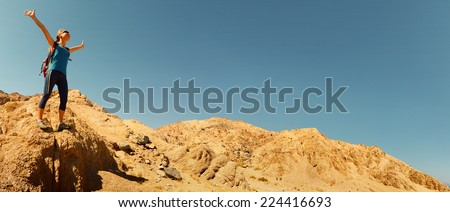 Hiker with raised hands standing on rocky ground in the desert