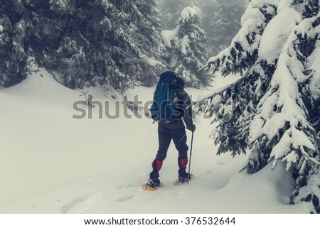 hiker with snowshoes in winter.Instagram filter. - stock photo