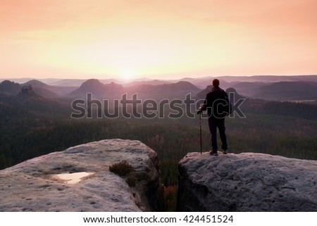 Hiker with sporty backpack stand on rocky view point above misty valley.  Sunny spring daybreak in rocky mountains. - stock photo