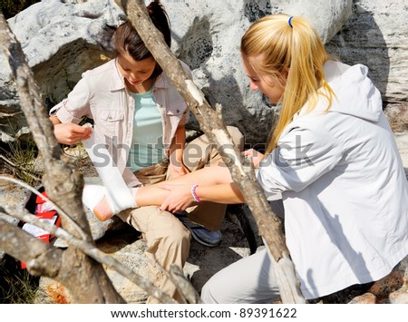 hiker with sprained ankle is helped by her friend with first aid kit for outdoor emergency - stock photo
