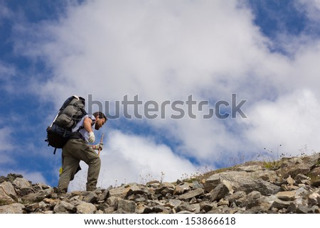 hiker with stick on a background of sky