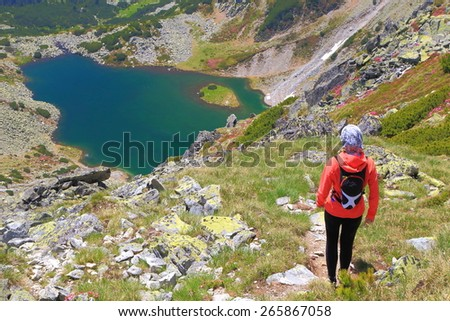 Hiker woman above distant lake in sunny day of summer - stock photo