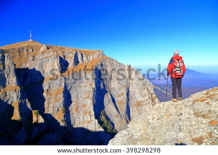 Hiker woman admires the view from the mountain edge in Bucegi massif, Romania - stock photo