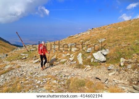 Hiker woman along sunny trail in Fagaras mountains, Romania - stock photo