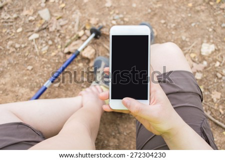 Hiker woman asking medical help with your phone after an accident - stock photo
