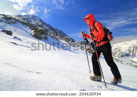 Hiker woman climbs a snow covered trail in winter - stock photo