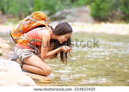 Hiker woman drinking water from river creek hiking in Zion National Park. Happy female hiker taking break drinking fresh water in Zion Canyon wearing backpack. Healthy lifestyle with girl in Utah, USA - stock photo