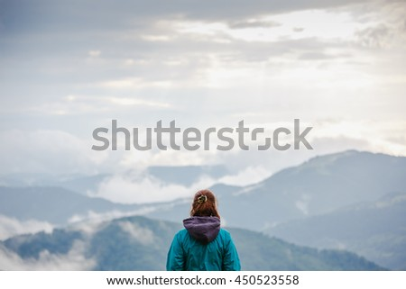 Hiker woman enjoying landscape of cloudy mountains, rear view - stock photo