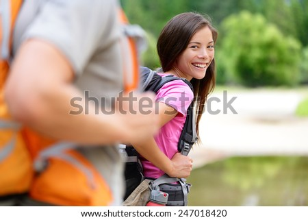 Hiker. Woman hiking smiling happy on trek with backpack during summer outdoors activity. Multiethnic Asian Caucasian female model walking with a group on a day excursion trip hike in the forest. - stock photo