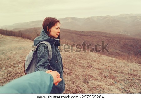 Hiker woman holding man's hand on nature in the mountains. Couple in love. Focus on woman. Point of view shot - stock photo