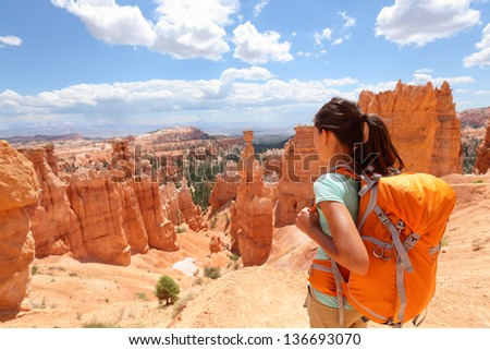 Hiker woman in Bryce Canyon hiking looking and enjoying view during her hike wearing hikers backpack. Bryce Canyon National Park landscape, Utah, United States. - stock photo