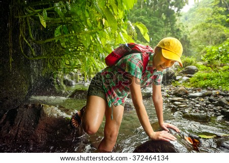 Hiker woman in hiking overcomes river in rain forest. Happy girl smiling enjoying outdoors summer trekking vacation. - stock photo