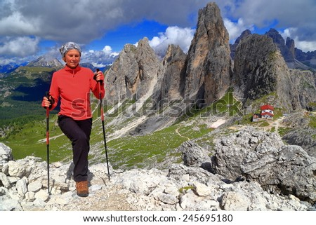 Hiker woman in sunny trail with Torre Wundt and Savio Fonda refuge in the background, Cadini di Misurina, Dolomite Alps, Italy - stock photo