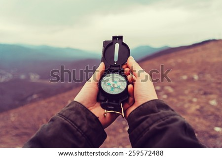 Hiker woman searching direction with a compass in the mountains. Point of view shot - stock photo