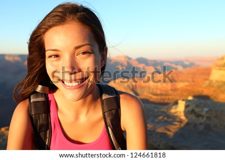 Hiker woman smiling natural canidid in happy outdoor portrait. Aspirational lifestyle image of hiking young multiracial female hiker in Grand Canyon, South Rim, Arizona, USA. - stock photo
