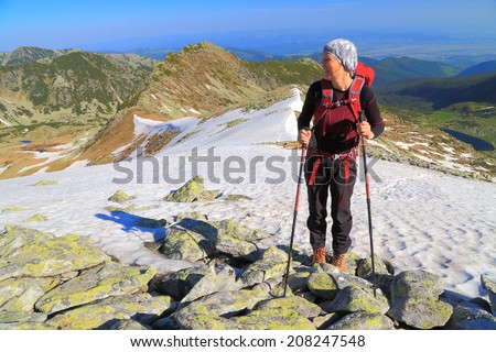 Hiker woman standing on the mountain in sunny morning - stock photo