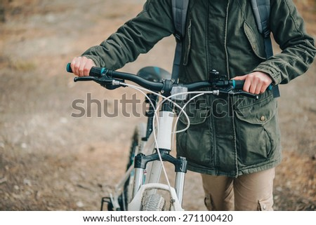 Hiker woman walking with bicycle in the forest, close-up - stock photo