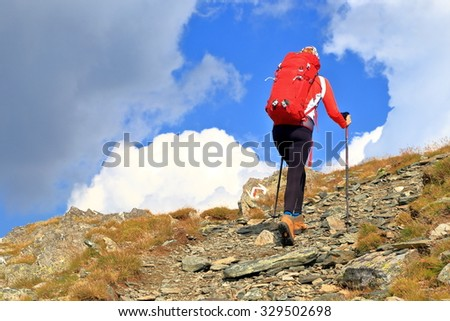 Hiker woman with a red backpack on a mountain trail under the clouds - stock photo