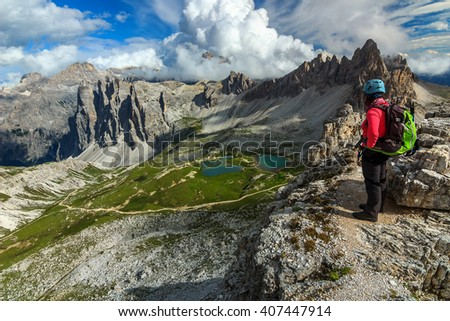 Hiker woman with backpack and mountain equipment,looking at view the Piani alpine glacier lakes,Dolomites,Italy,Europe - stock photo