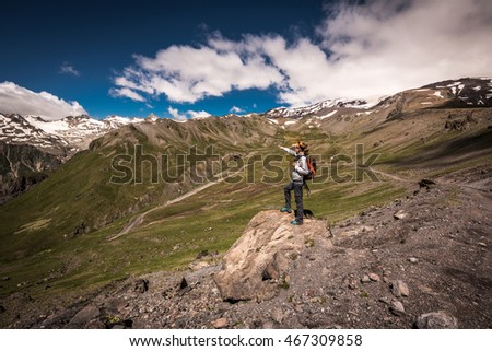 Hiker woman with backpack standing on top of a mountain and enjoying valley view