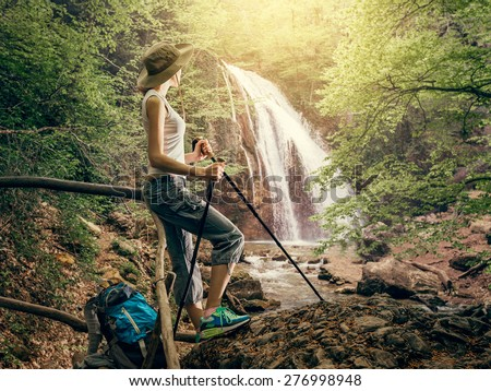 Hiker woman with backpack walking on a forest trail in the mountains on the background a waterfall. Hiking. Adventure in the forest. - stock photo