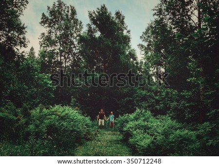 Hiker young couple walking among beautiful old trees in the summer green forest - stock photo