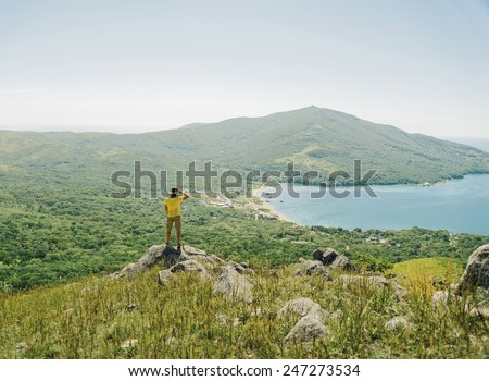 Hiker young man standing on peak of rock and looking into the distance to mountain and sea in summer - stock photo