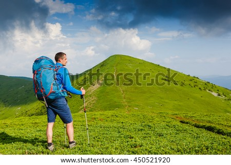 Hiker young man with backpack and trekking poles looking at the mountains in summer outdoor