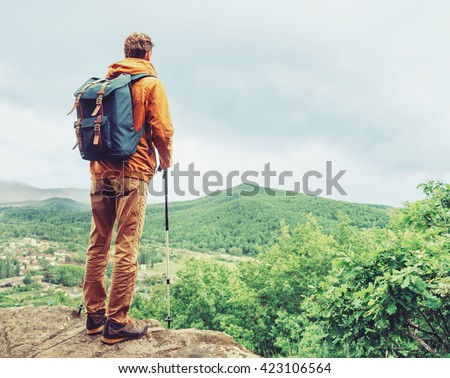 Hiker young man with backpack and trekking poles standing on edge of cliff and looking at the mountains in summer outdoor, rear view - stock photo