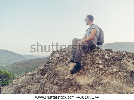 Hiker young man with backpack sitting on peak of rock on background of mountains and enjoying view of landscape in summer outdoor - stock photo